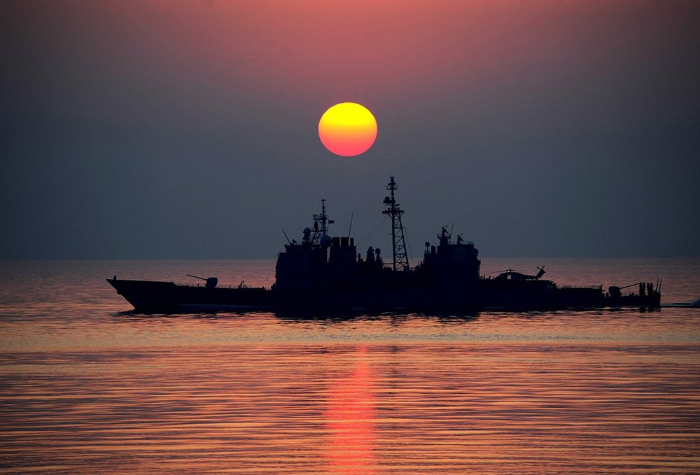 A Navy ship navigates calm waters on a sunset. I Image: Pixabay.