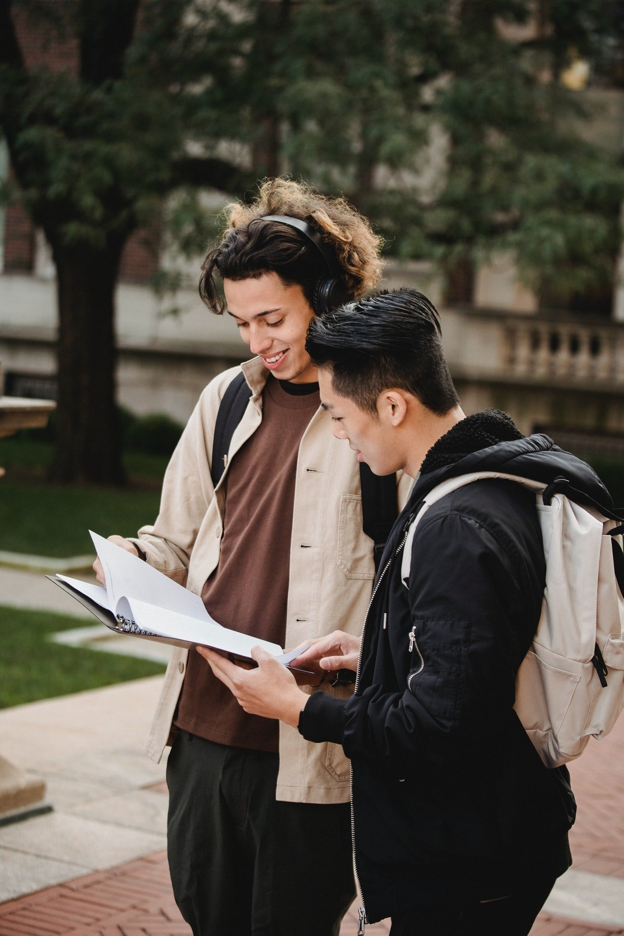 Two students looking at their notebook | Source: Pexels