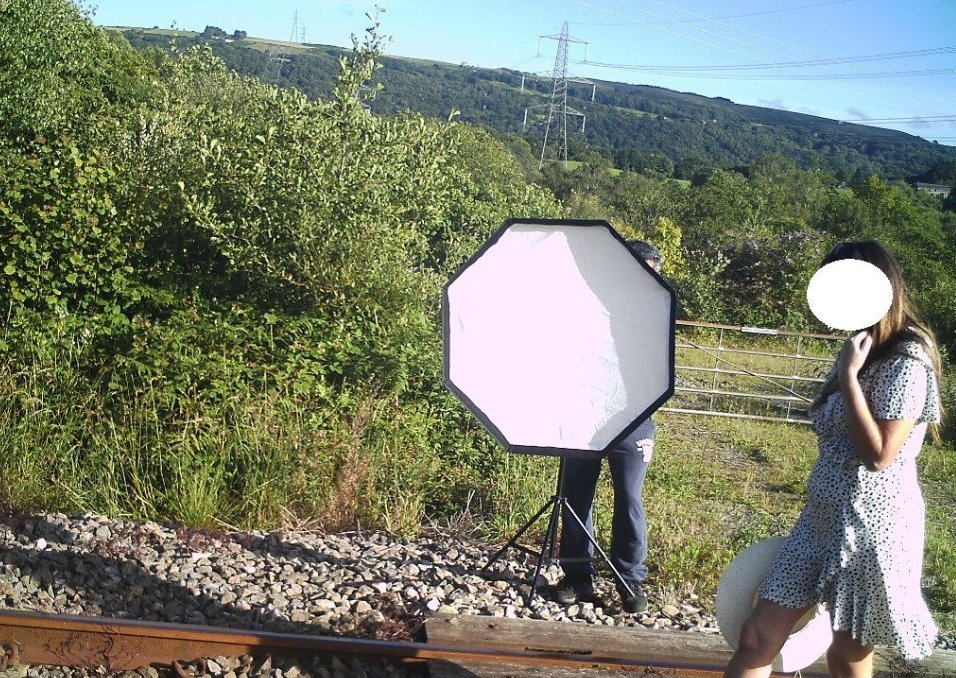 Woman walking on a railroad track while a man uses a studio light to take photographs of her. │ Source: twitter.com/WalesOnline
