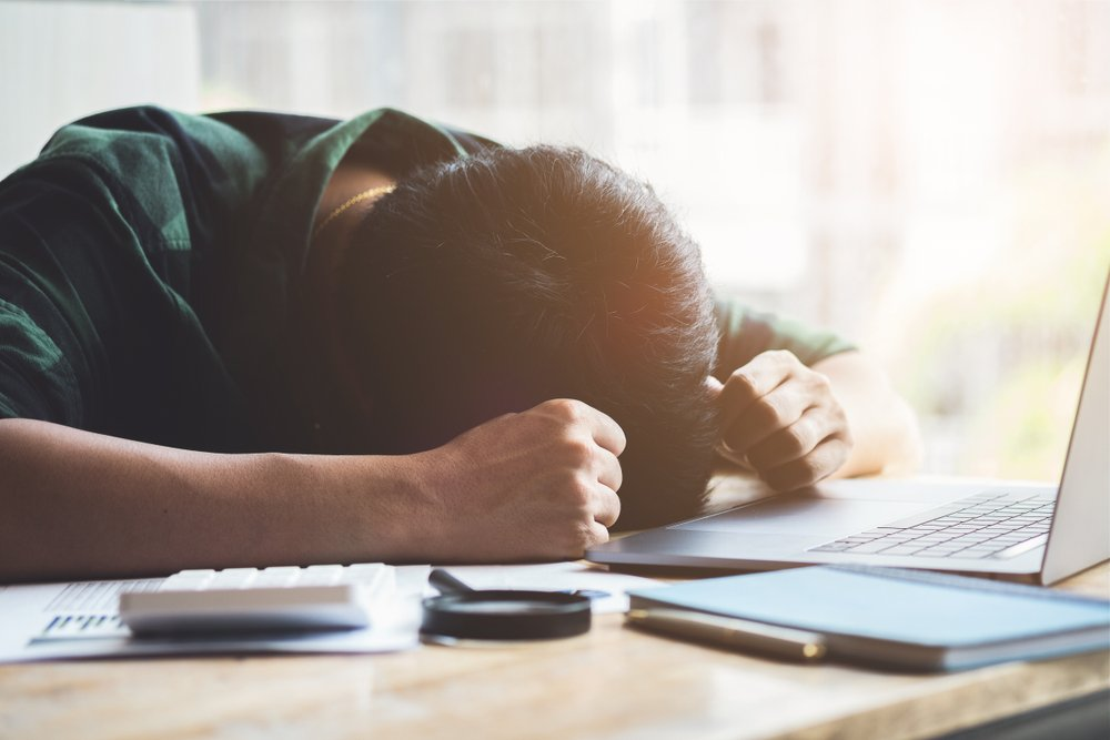 A man suffering burnout syndrome and sleeping at his desk. | Photo: Shutterstock