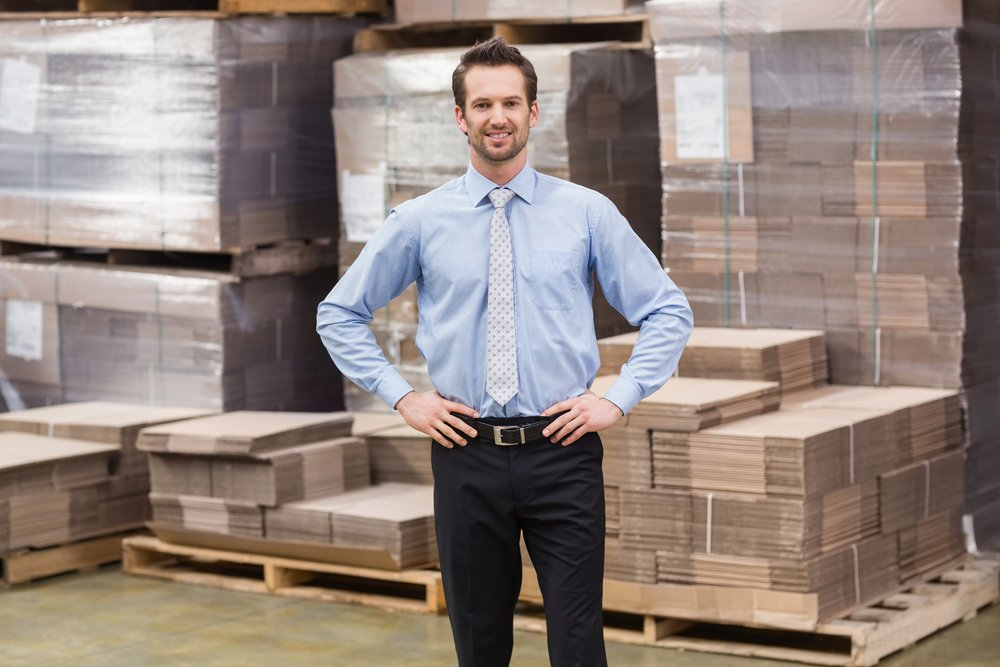 A smiling manager placing his hands on his hips in a large warehouse. | Photo: Shutterstock.