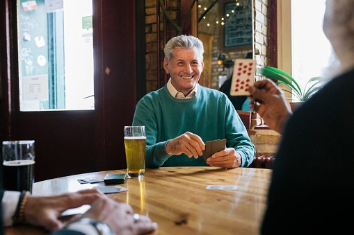 Photo of a mature man smiling and enjoying a card game with his friends at their local bar. | Photo: Getty Images