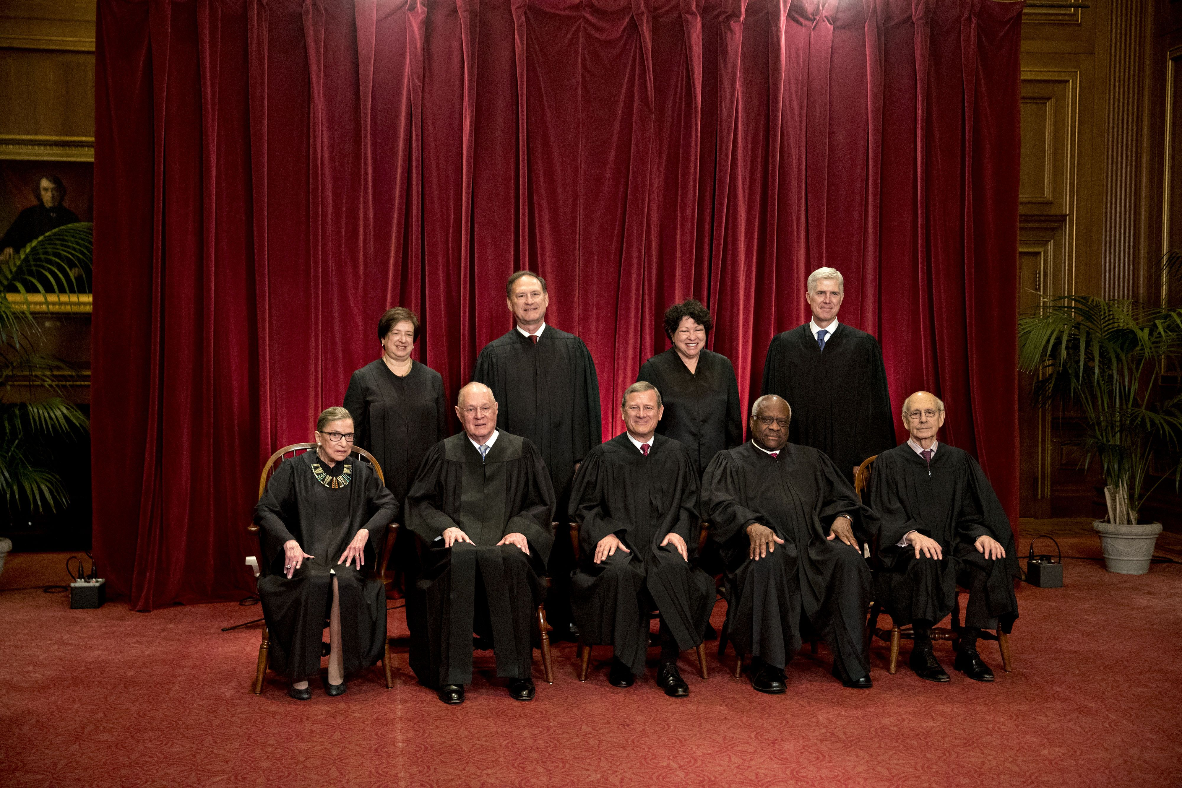 (L-R) Associate Justice Ruth Bader Ginsburg, Associate Justice Anthony Kennedy, Chief Justice John Roberts, Associate Justice Clarence Thomas, and Associate Justice Stephen Breyer. Standing left to right; Associate Justice Elena Kagan, Associate Justice Samuel Alito Jr., Associate Justice Sonia Sotomayor, and Associate Justice Neil Gorsuch during their formal group photograph in the East Conference Room of the Supreme Court in Washington, D.C., U.S., on Thursday, June 1, 2017. | Source: Getty Images