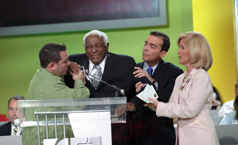 Omar Pardillo, Ambrocio Hernández y Lourdes Meneses ayudan a Pedro Knight durante un evento de la Liga Contra El Cáncer el 6 de junio de 2004 en Miami, Florida. Knight fue hospitalizado por hipoglicemia poco después. || Fuente: Getty Images