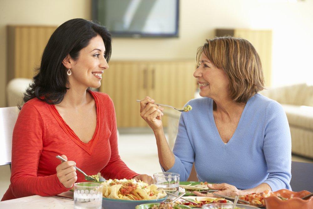 Madre hispana con hija adulta disfrutando de una comida en casa. Fuente: Shutterstock