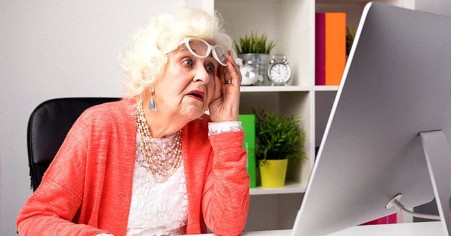 An elderly woman looking at the computer monitor. | Source: Shutterstock