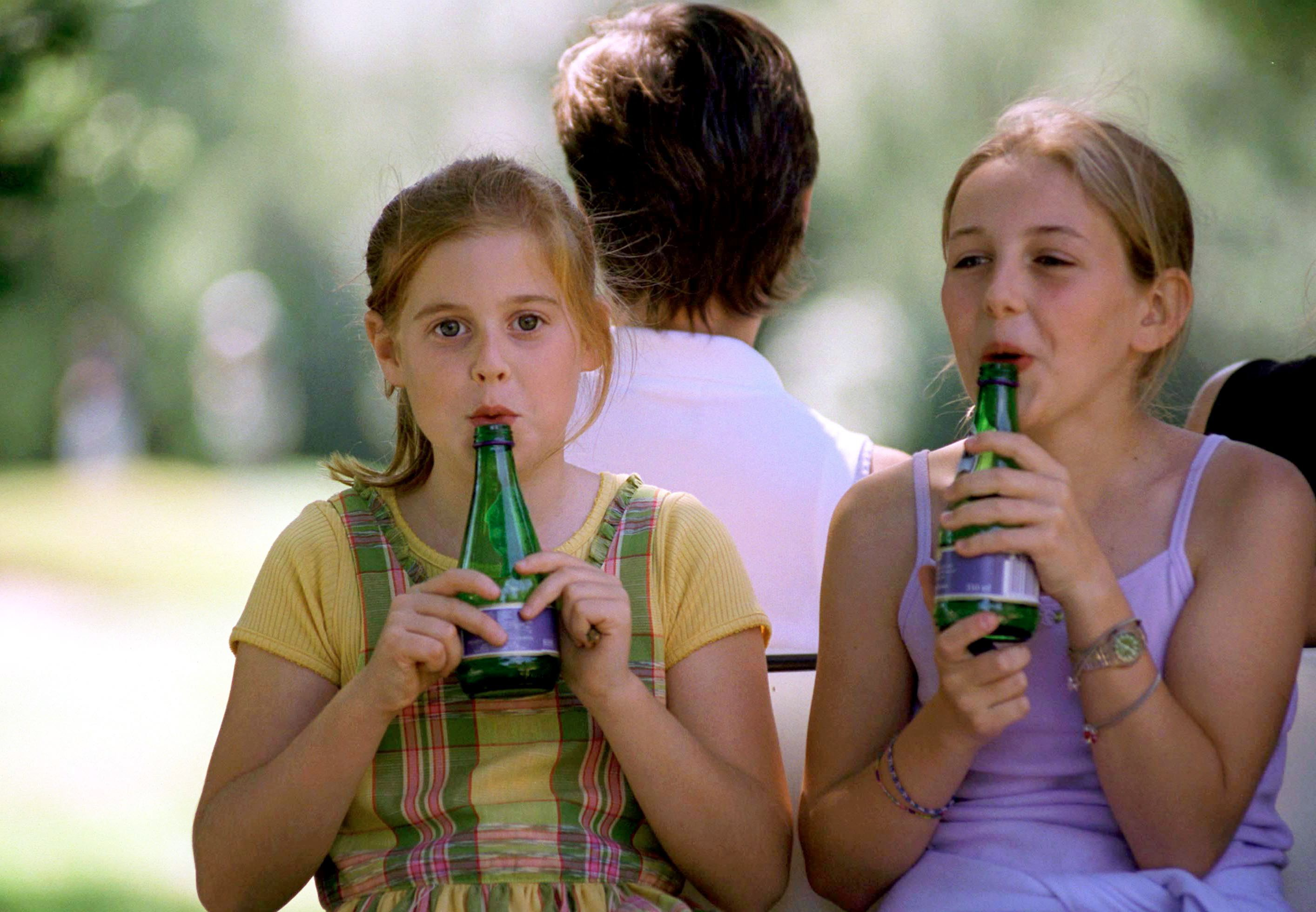 WENTWORTH, UNITED KINGDOM - JULY 19: Princess Beatrice And Her School Friend Laura Gallacher [11-year-old Daughter Of International Golfer Bernie Gallacher] Having Fun Making Tunes By Blowing Across The Tops Of Bottles At Wentworth Golf Club Charity Golf Tournament In Aid Of Children In Crisis. (Photo by Tim Graham Photo Library via Getty Images)