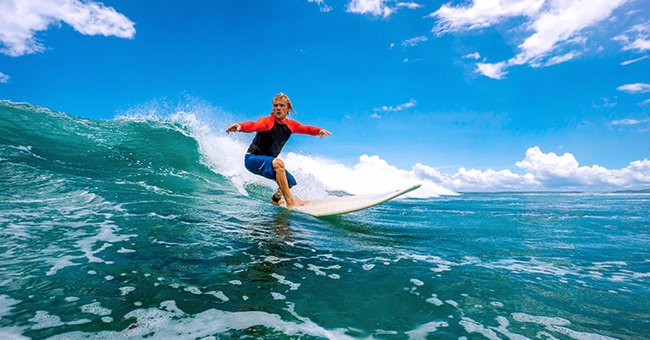 A teenager surfing in the ocean | Photo: Shutterstock