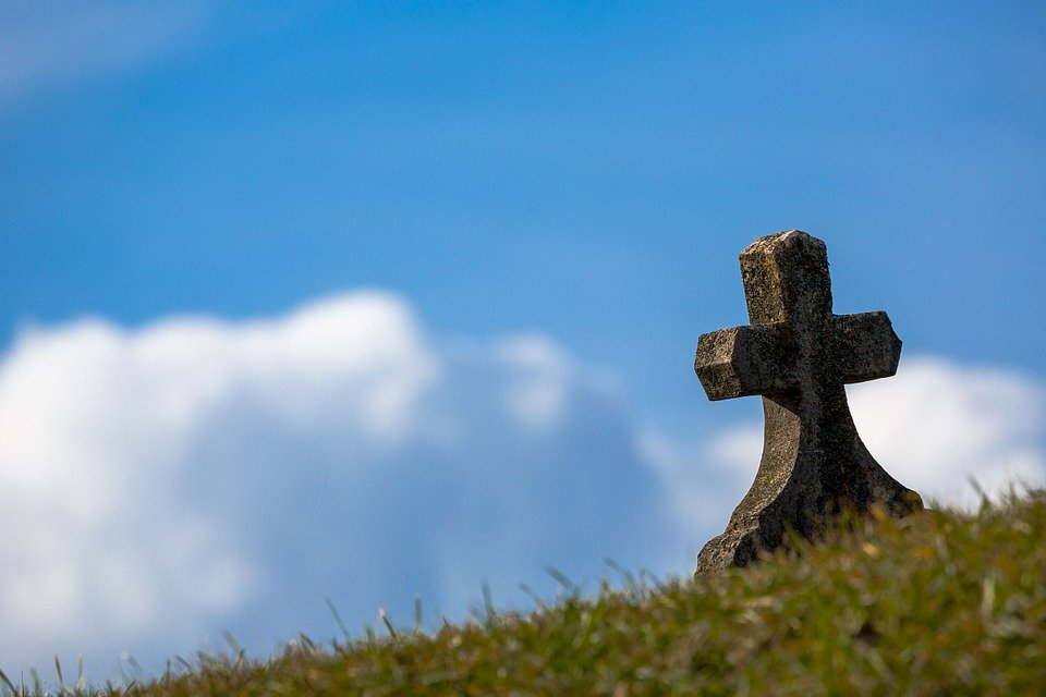 A cross on top of a grave on a sunny day.   Source: Pixabay