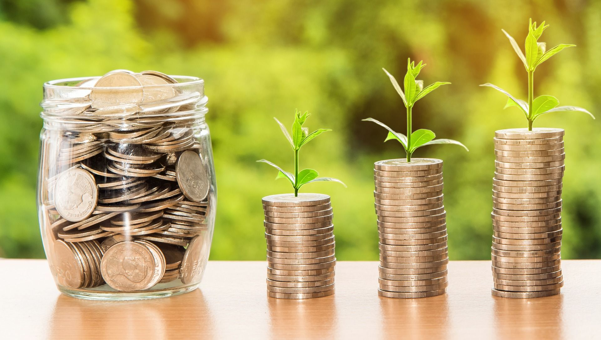 Coins in a jar next to stacked up coins with small plants sprouting out of them. | Source: Shutterstock