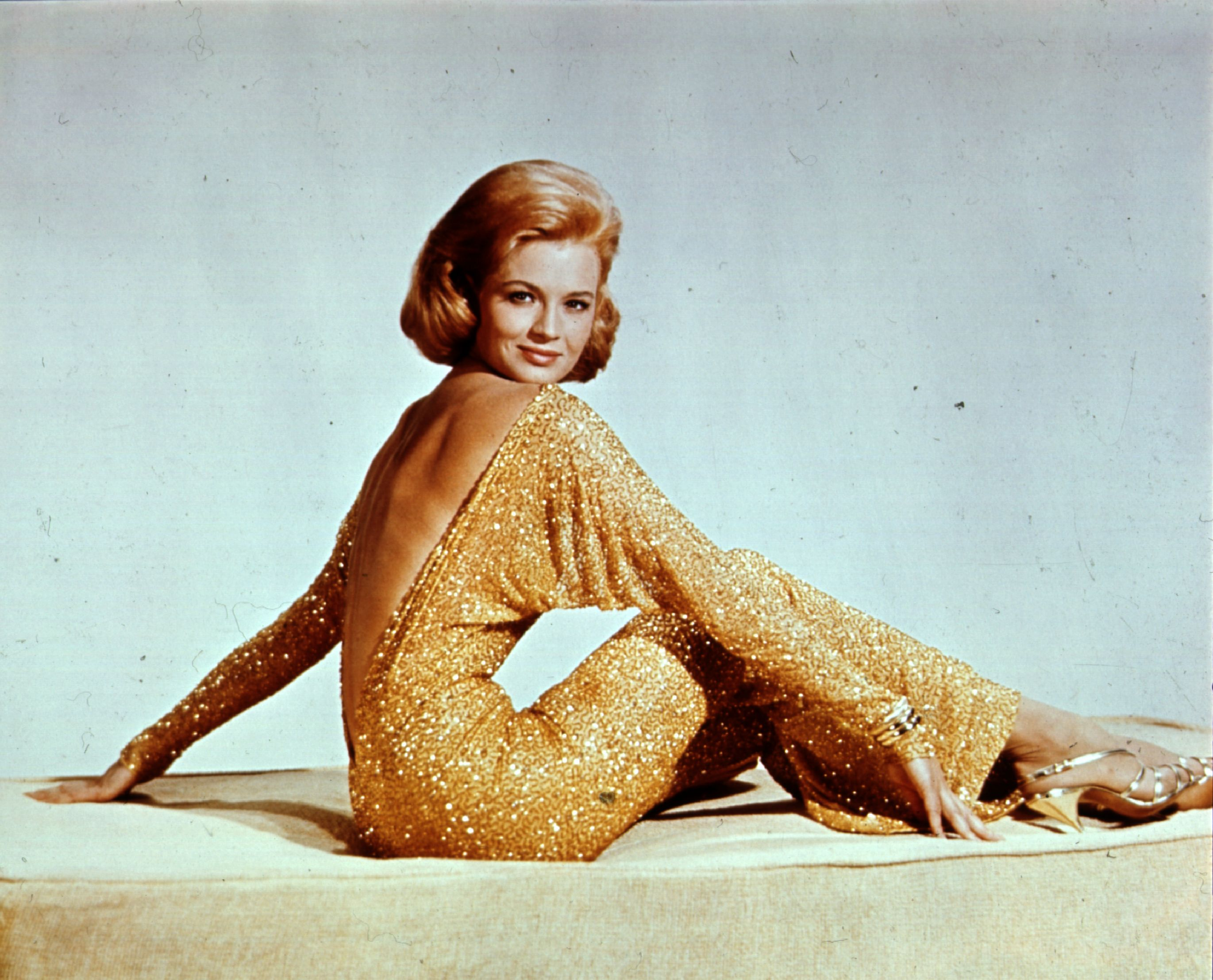 Angie Dickinson wearing a backless gold lame evening dress with batwing sleeves circa 1965. | Photo: Getty Images