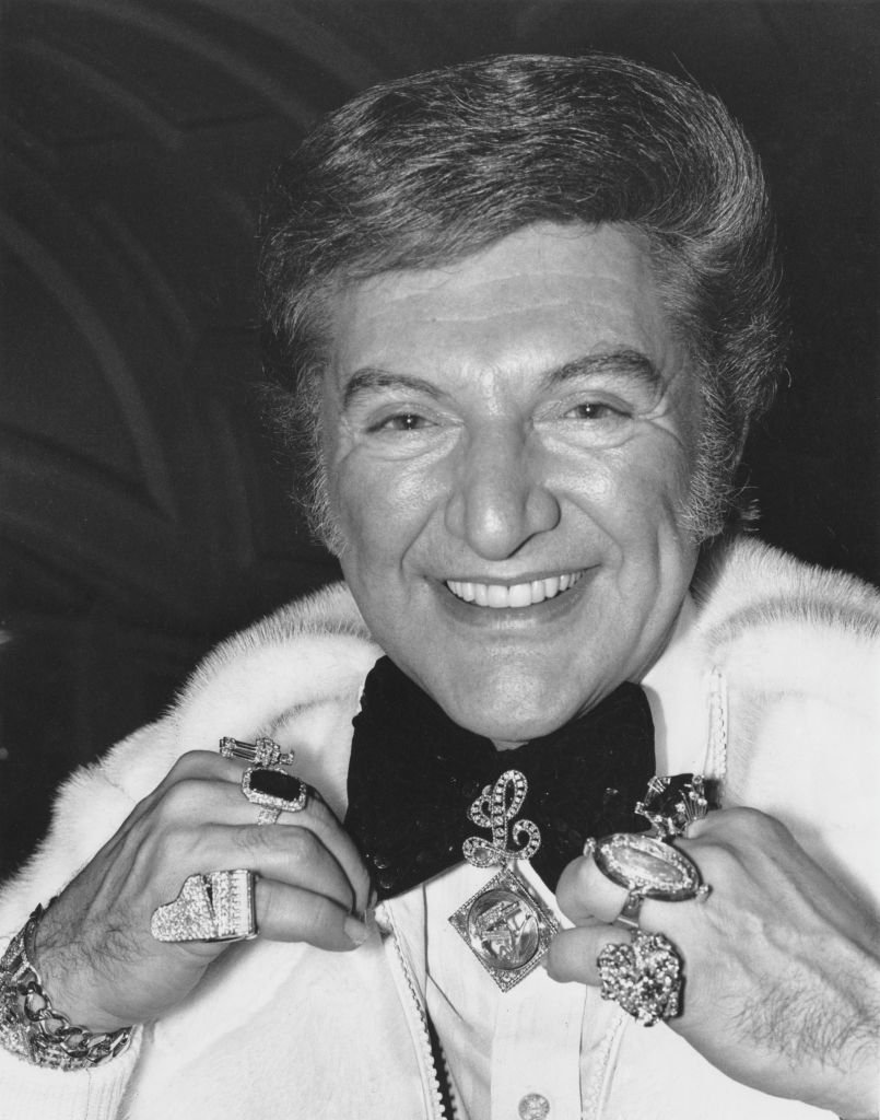 Liberace, born Wladziu Valentino Liberace (1919 - 1987), showing off some of his jewellery upon his arrival in London | Getty Images