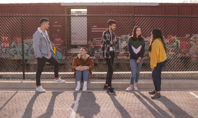 Group of five teenagers in front of chain link fence | Source: Unsplash