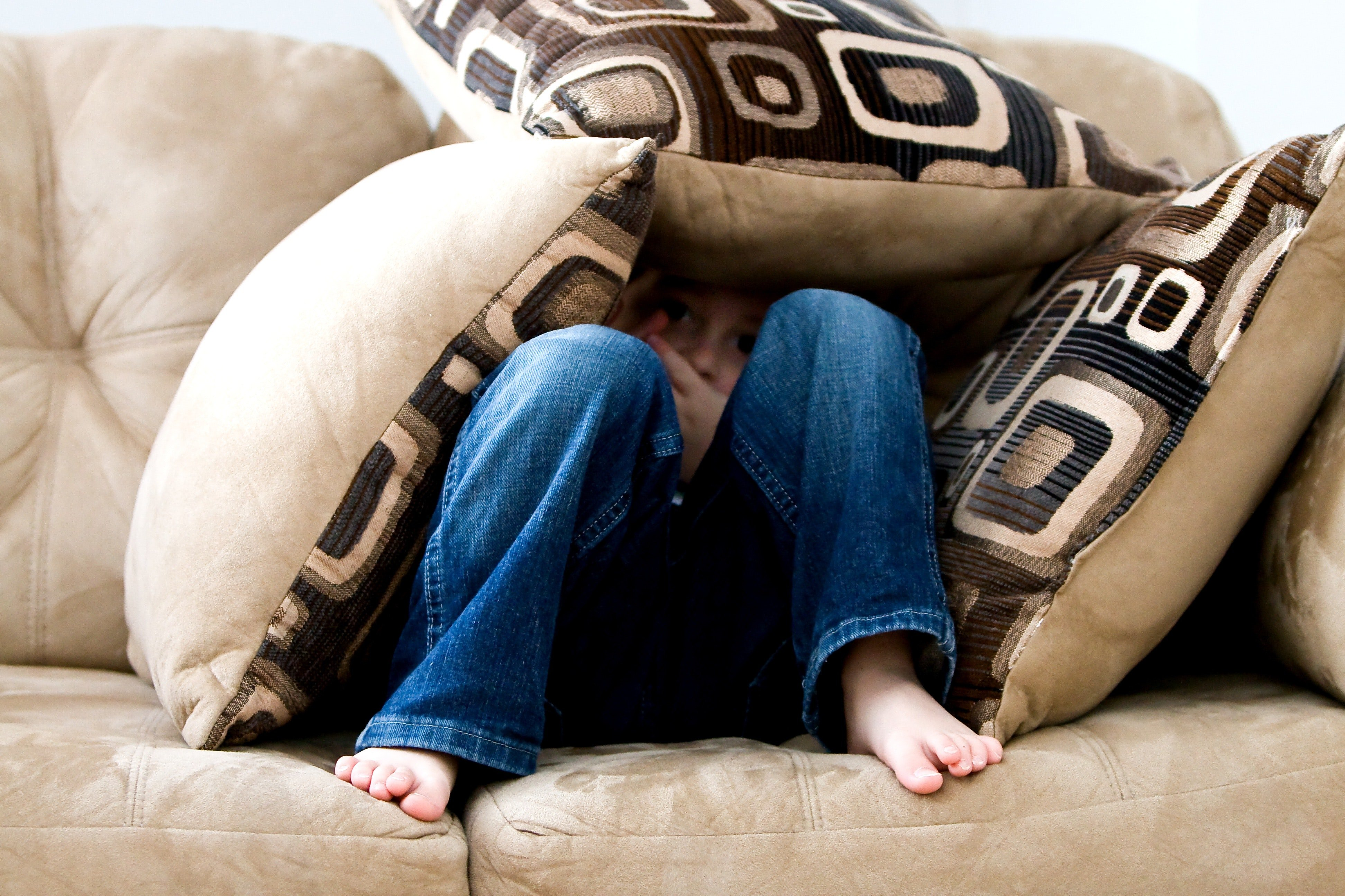 A young kid hides under the cushions of a couch.   Source: Pexels