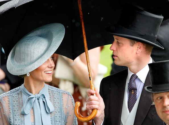 Catherine, Duchess of Cambridge and Prince William, Duke of Cambridge shelter under an umbrella as they attend day one of Royal Ascot at Ascot Racecourse | Photo: Getty Images
