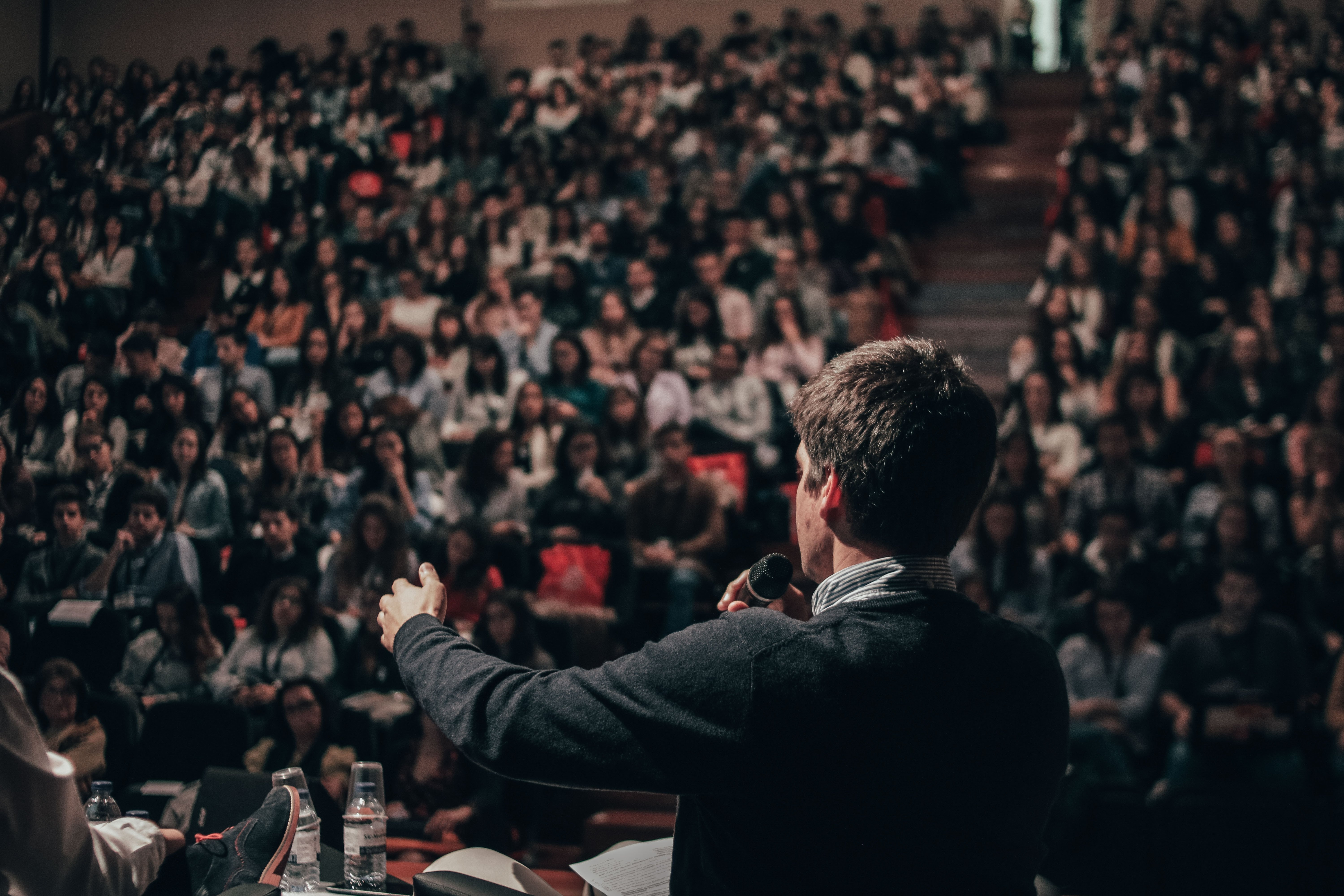 Man speaking in front of an audience. | Source: Unsplash