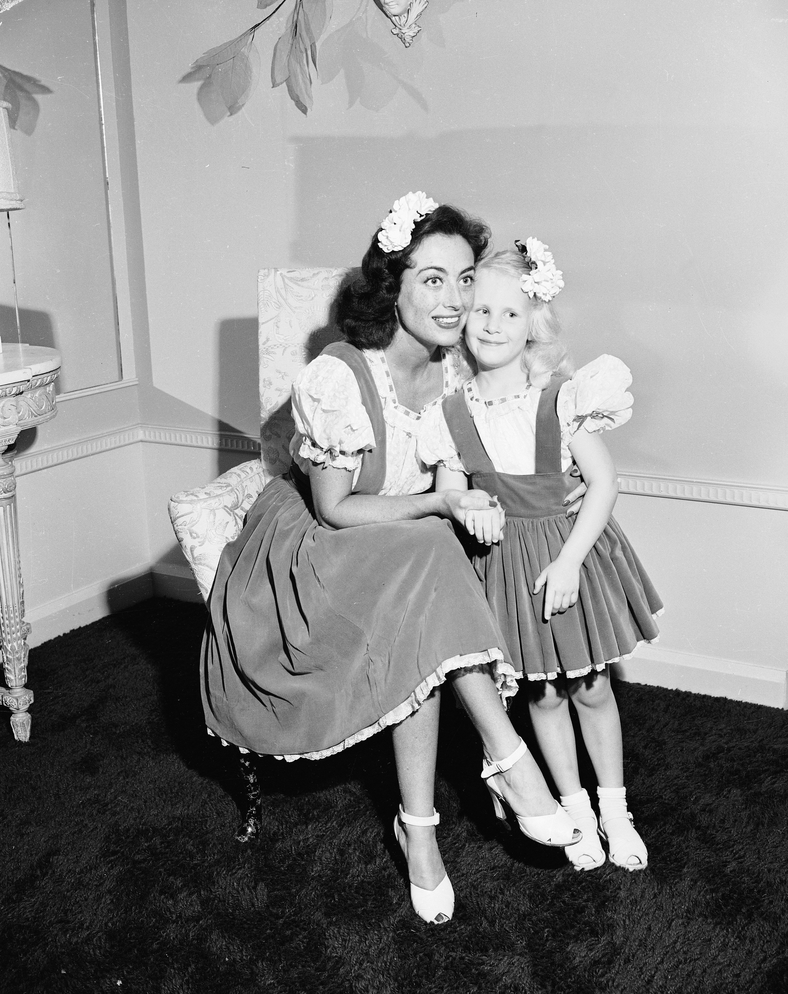 American actor Joan Crawford (1904 - 1977) hugs her adopted daughter Christina, wearing matching outfits, June 1944.   Source: Getty Images
