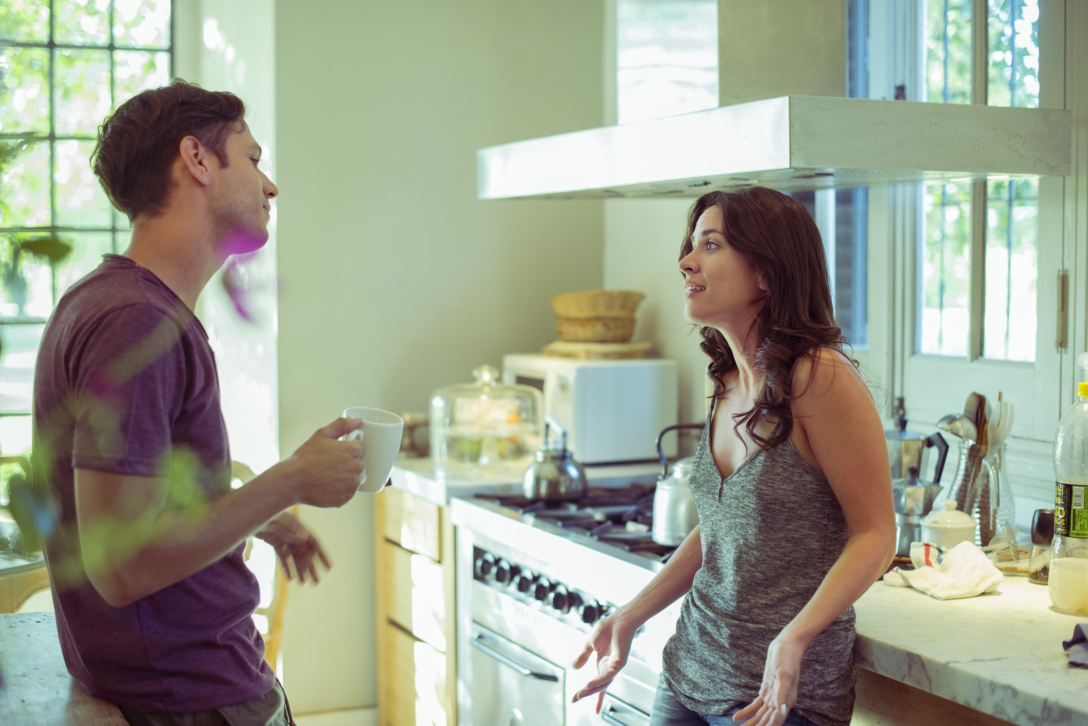 A photo of a couple talking in the kitchen. | Photo: Getty Images