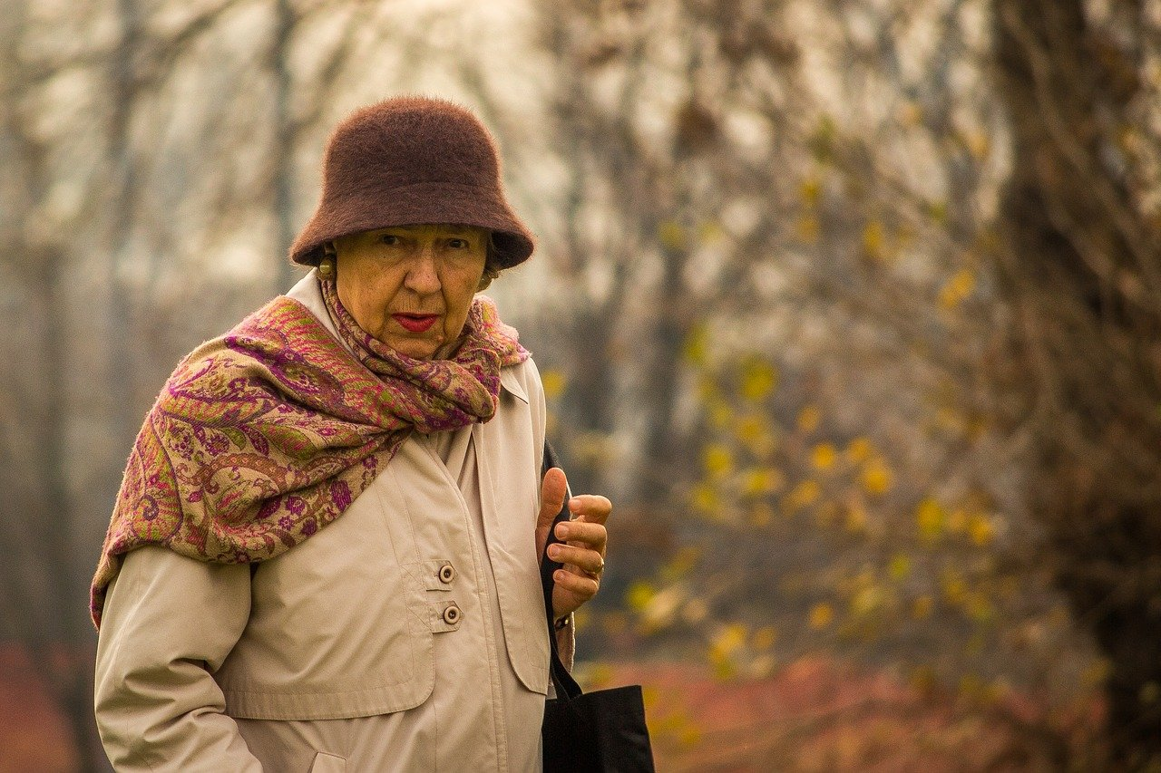 Une vieille femme qui tient un sac à main   Source : Pixabay