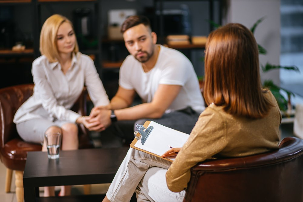 A married couple sitting together in a psychologist office sharing opinions and experiences | Photo: Shutterstock