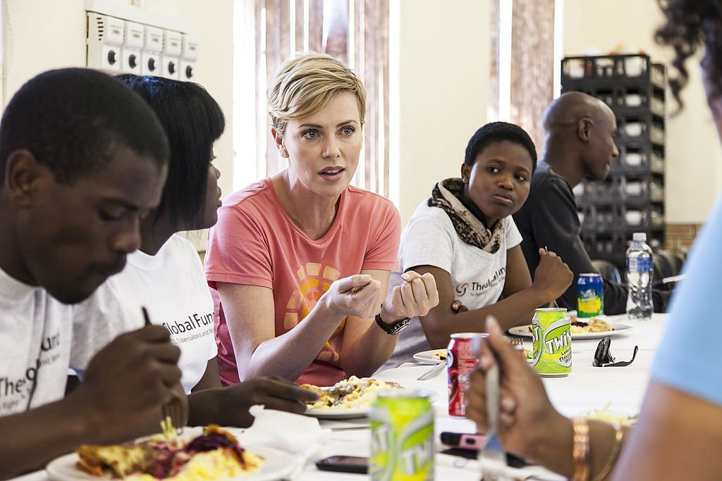 Charlize Theron visiting a Youth Ambassador Project funded by the Global Fund to Fight Aids in August 2013. | Photo: Getty Images
