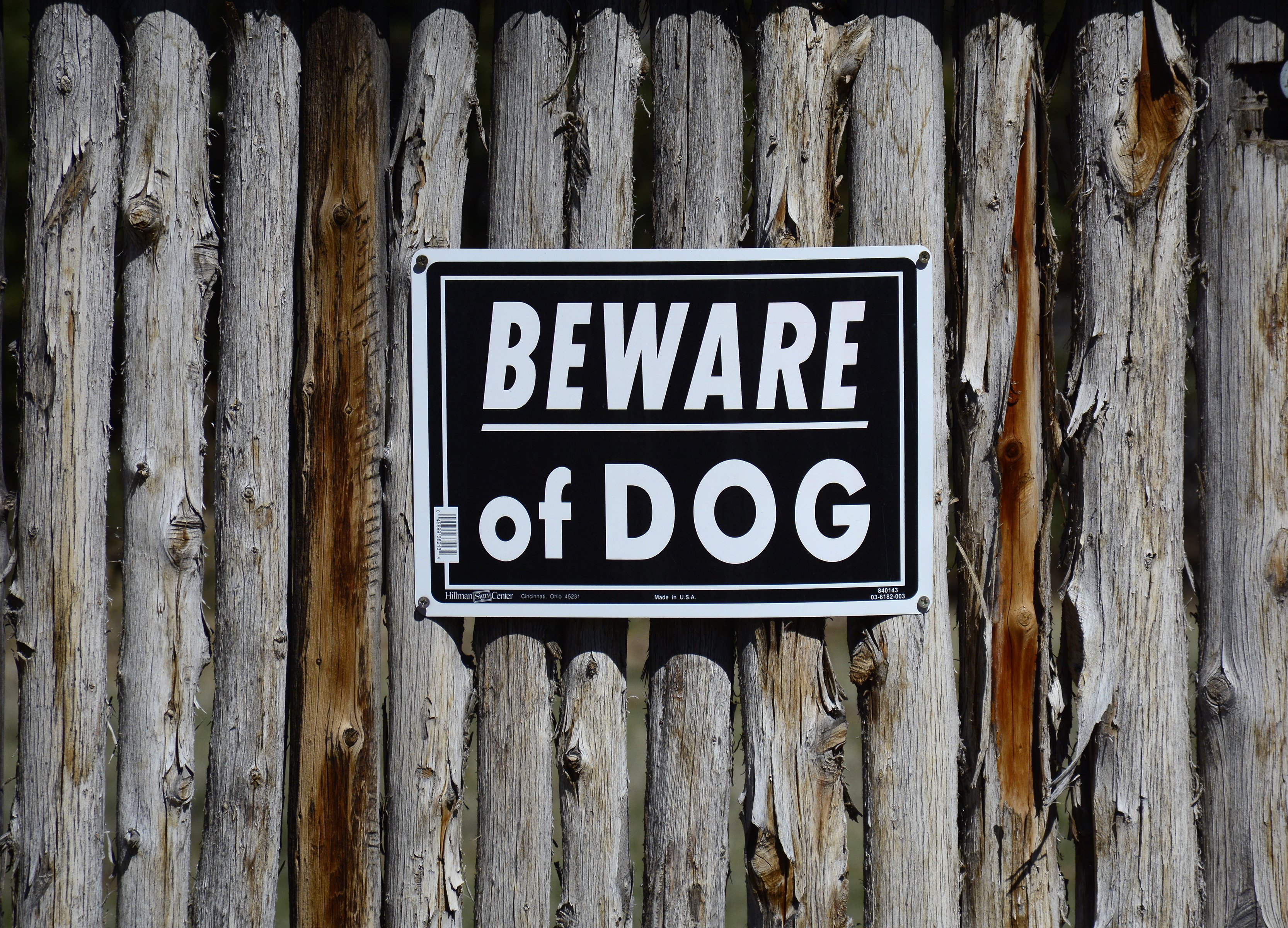 A 'Beware of Dog' sign is mounted to a rustic yard fence in Santa Fe, New Mexico. MAY 14, 2017 |Photo: Getty Images