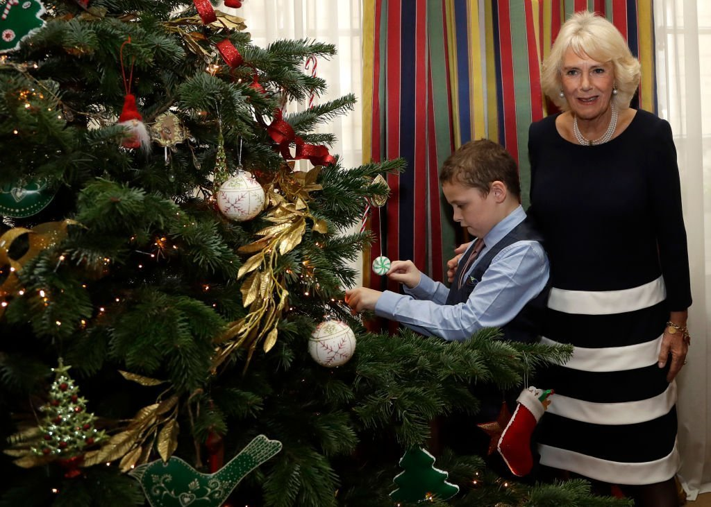 Camilla, Duchess of Cornwall helps Aidan Birnie, 9, to decorate the Christmas Tree. | Source: Getty Images