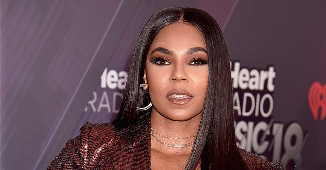 Ashanti Draws Attention to Her Stunning Legs in a Purple Bodysuit & Fishnet Tights (Photos)