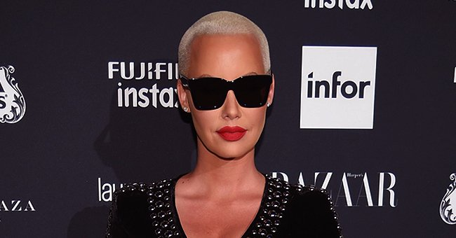 Amber Rose Looks Stunning Posing Poolside in a Tight Fitting Orange Dress