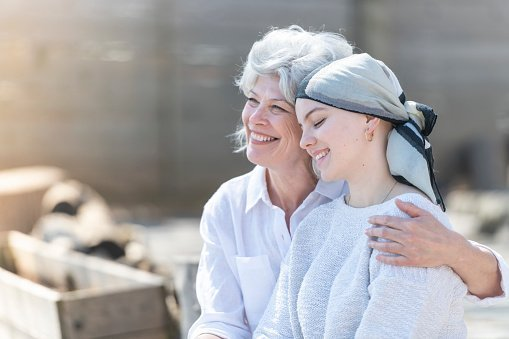 A beautiful young woman with cancer is wearing a head scarf and is embracing her mother. | Photo: Getty Images