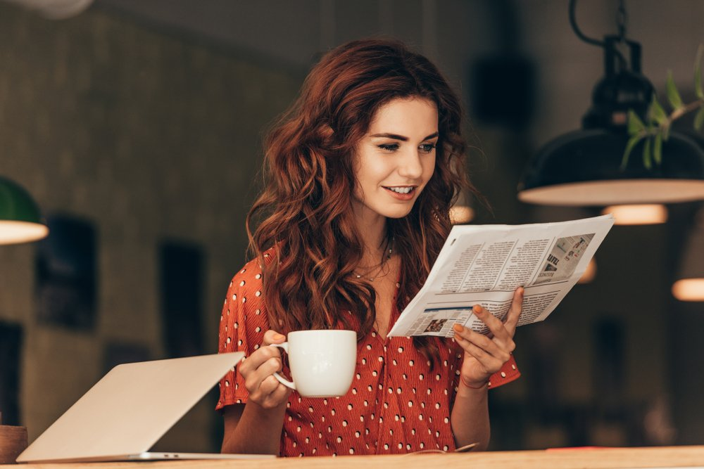 A woman holding a cup of coffee while reading a newspaper | Photo: Shutterstock