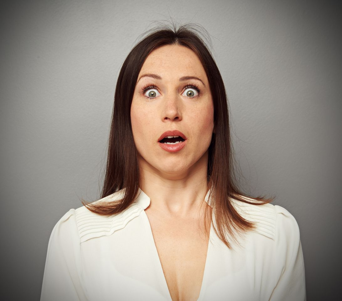 A woman looks at the camera with a shocked face. | Source: Shutterstock