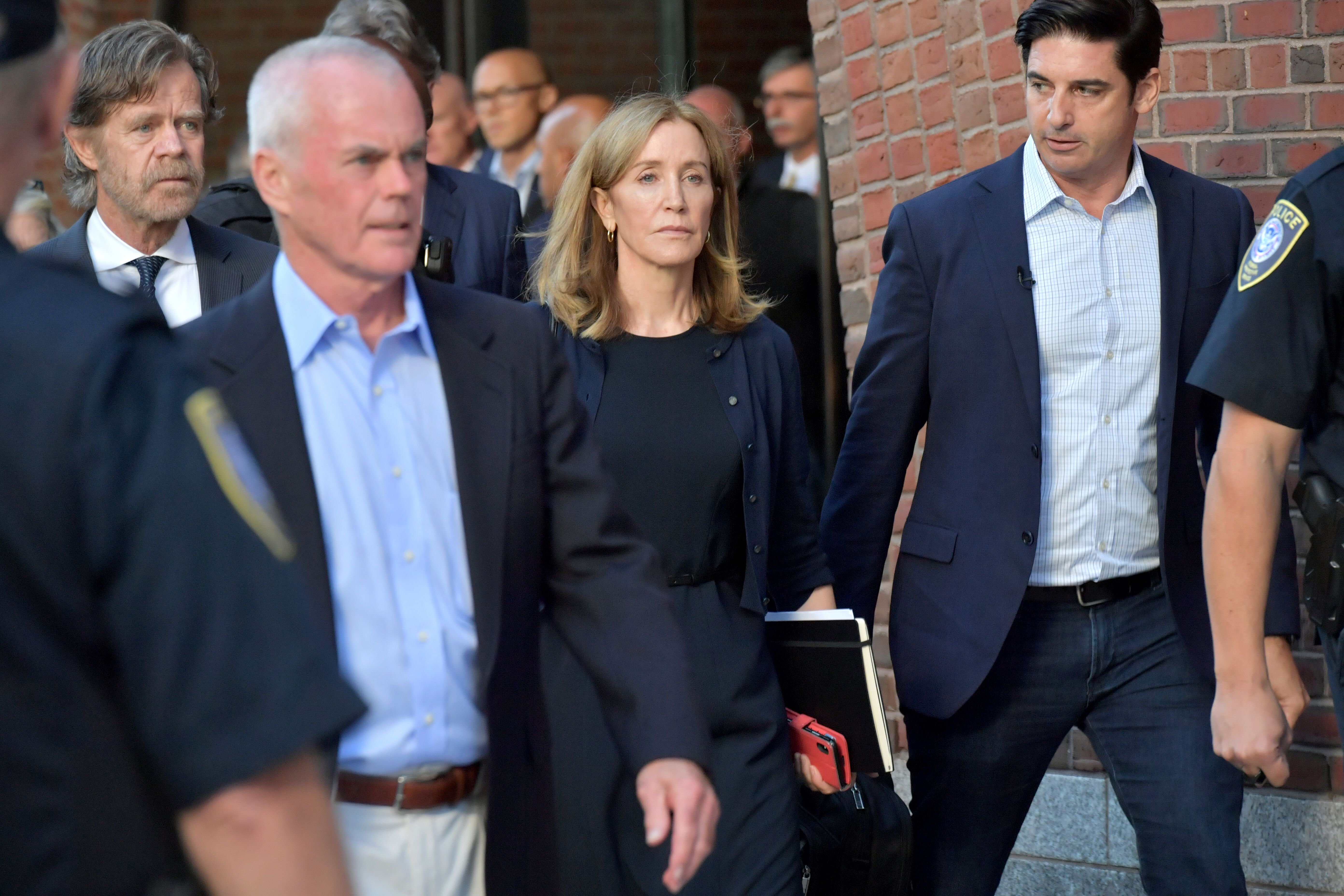 Felicity Huffman outside a Boston federal courthouse with her husband William H. Macy | Photo: Getty Images
