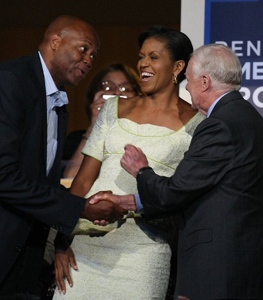 Craig Robinson shakes former president Jimmy Carter's hand as Michelle Obama looks on during day two of the Democratic National Convention (DNC) at the Pepsi Center August 26, 2008, in Denver, Colorado. | Source: Getty Images.