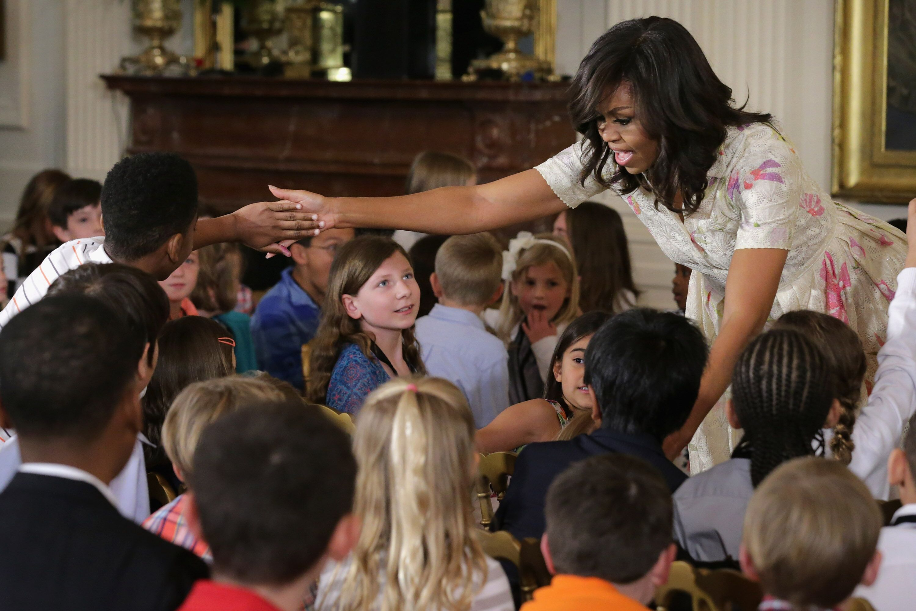 Michelle Obama gives hugs and high-fives to children for Take Our Daughters and Sons to Work Day in the East Room of the White House April 20, 2016 in Washington, DC. | Photo: Getty Images