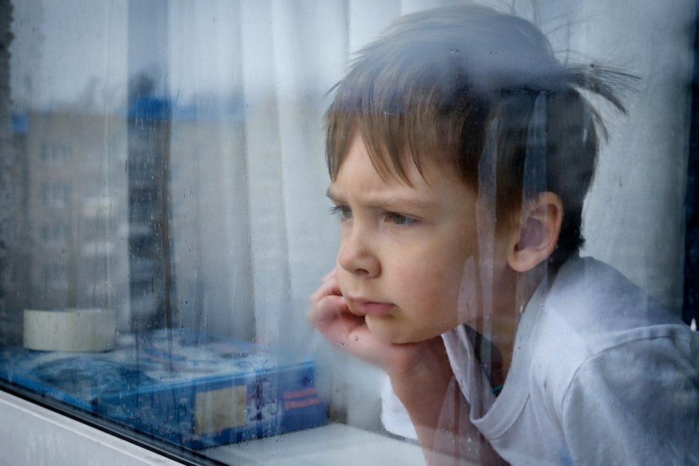 Little boy looks out raindrop-covered window | Photo: Shutterstock