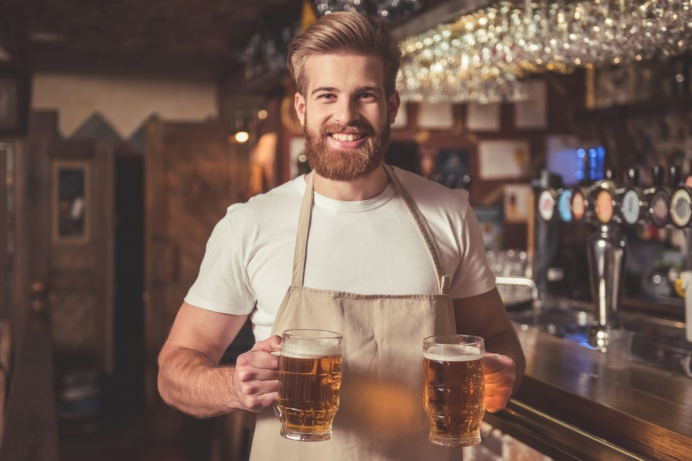 A bartender in apron, holding beer while standing near the bar counter in pub. | Photo: Shutterstock.