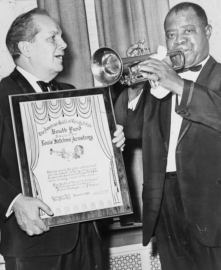Louis Armstrong plays trumpet with Joey Adams, president of the American Guild of Variety Artists Youth Fund. | Photo: Wikimedia Commons Images