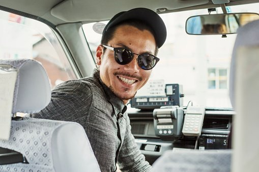 A man wearing sunglasses and baseball hat in the passenger seat of a car turning around and smiling | Photo: Getty Images