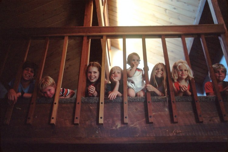 A photo of a large family with seven children peeking through a bannister railing on a staircase. | Photo: Unsplash.
