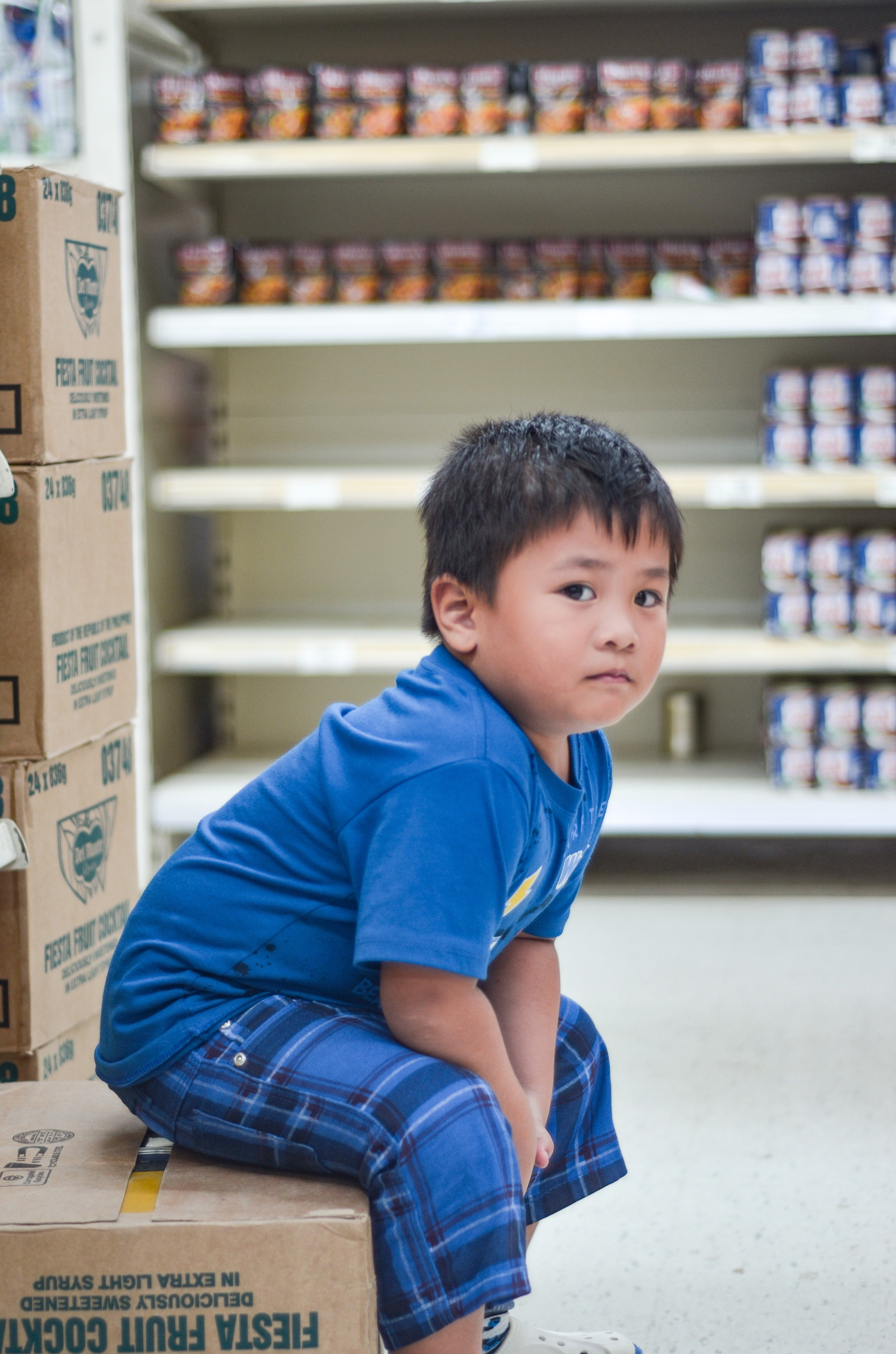 A young boy sitting on a cardboard box in a supermarket   Photo: Pexels