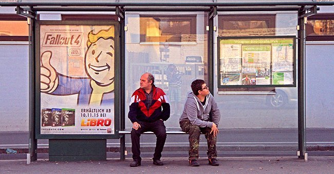 A man with a stutter conversing with another man at a bus station | Photo: Shutterstock