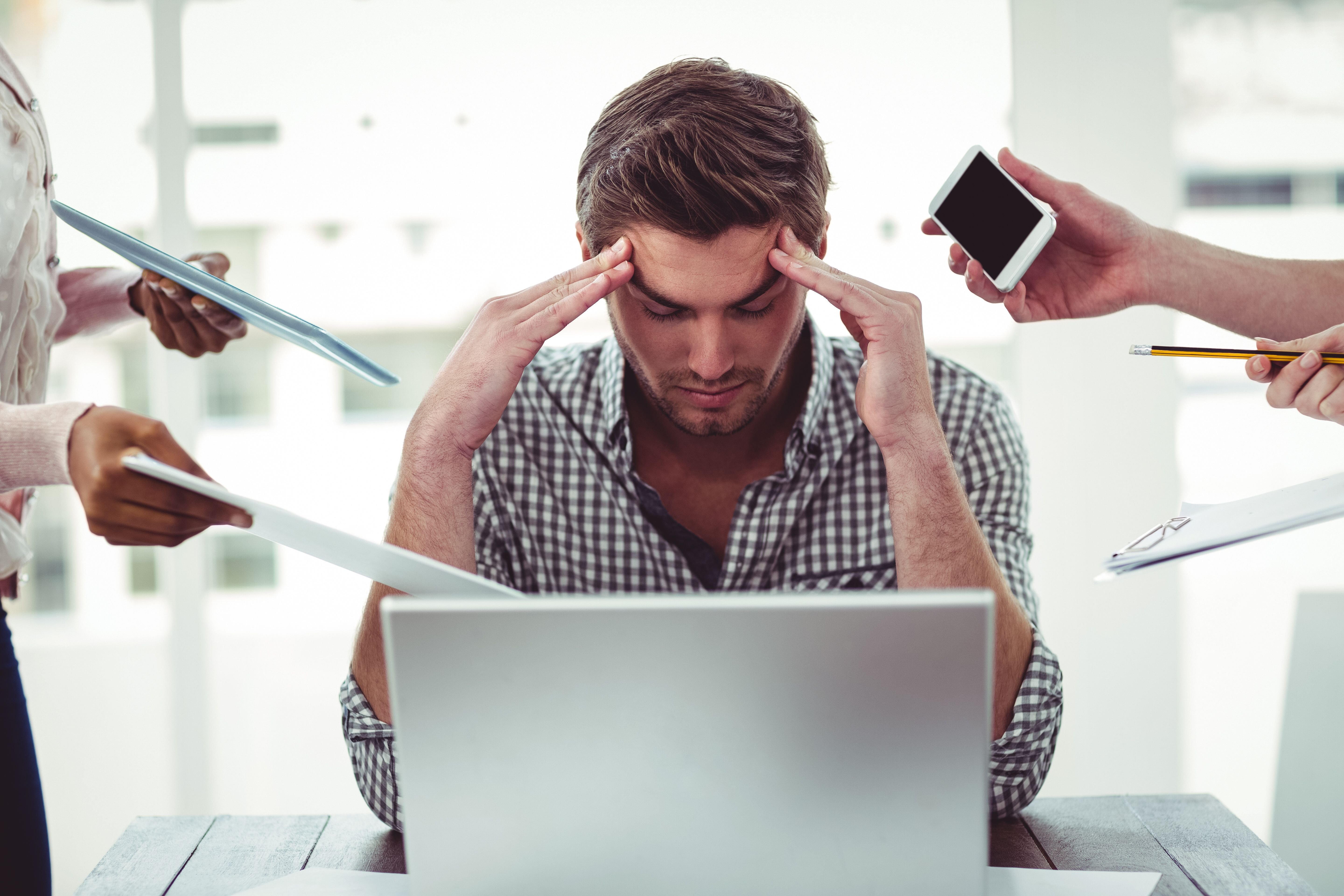 A man looks stressed at work.   Source: Shutterstock
