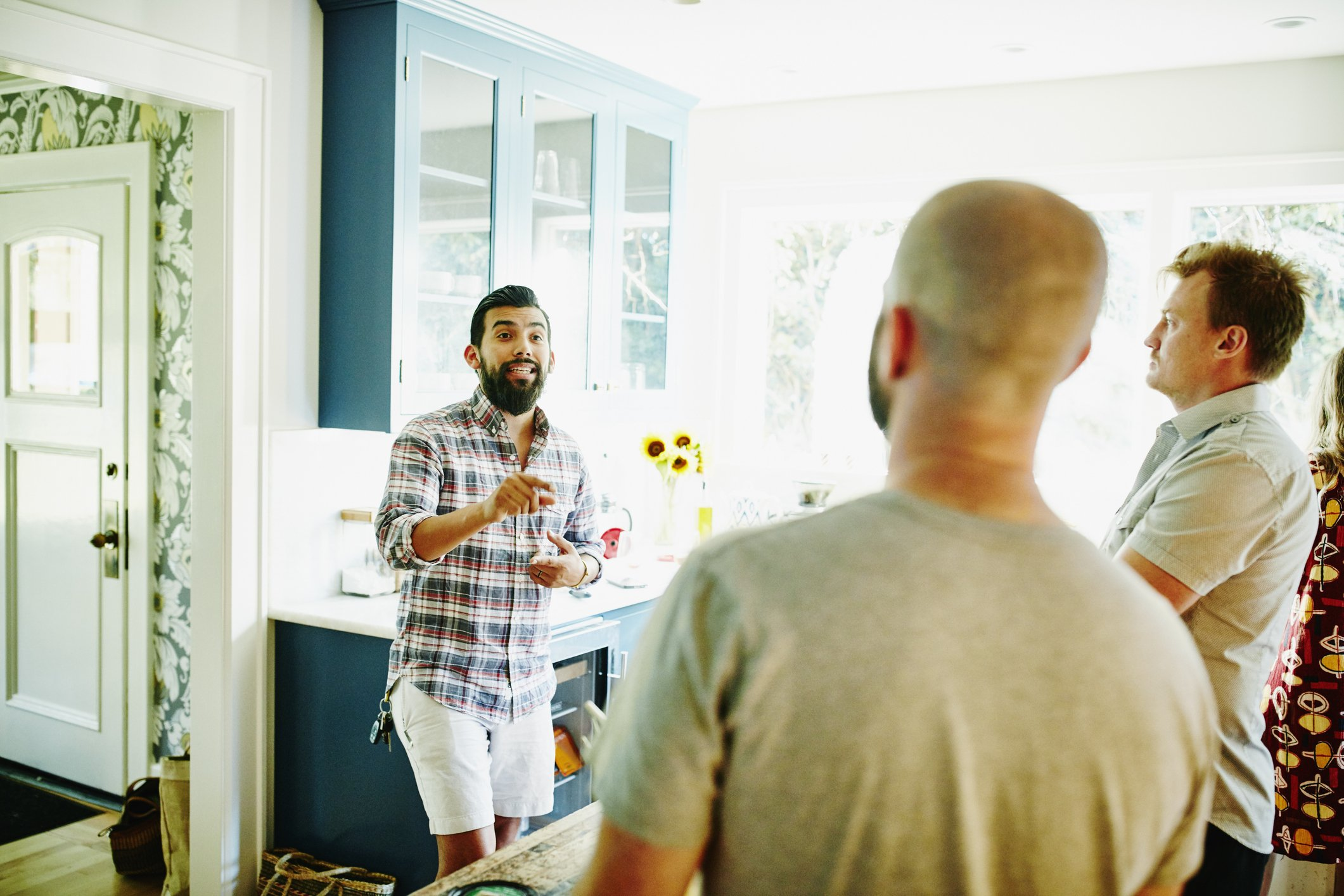 Man in discussion with friends in kitchen  | Photo: Getty Images