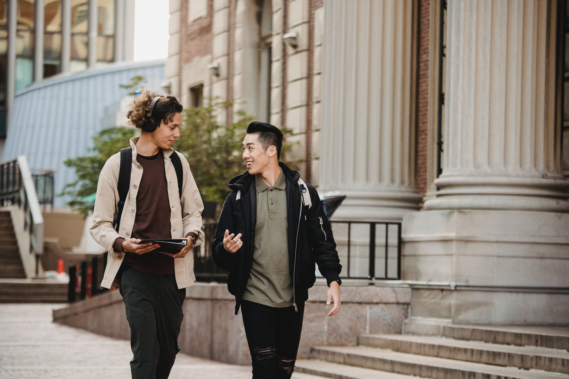 Two students talking and walking around campus | Source: Pexels