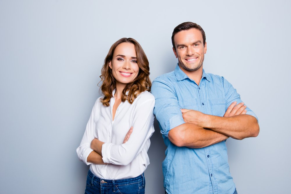 A happy male and female couple standing side-by-side and smiling together   Photo: Shutterstock/Roman Samborskyi