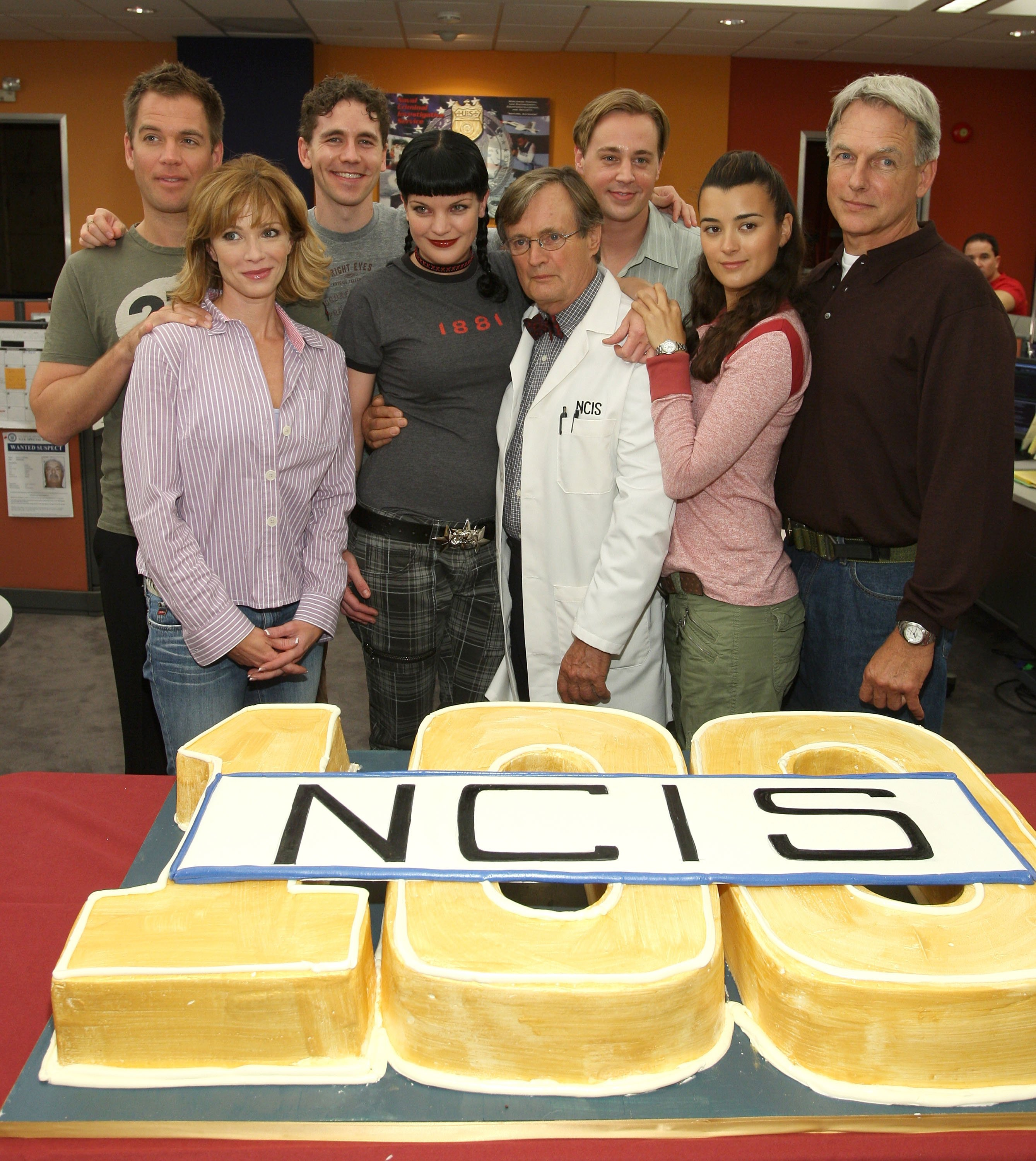 """The cast of """"NCIS"""" celebrating 100 episodes of the show with a large cake. 2007, California. 