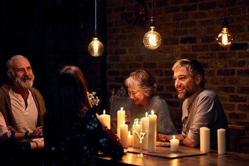 Photo of relaxed family group enjoying candlelit dinner together | Photo: Getty Images