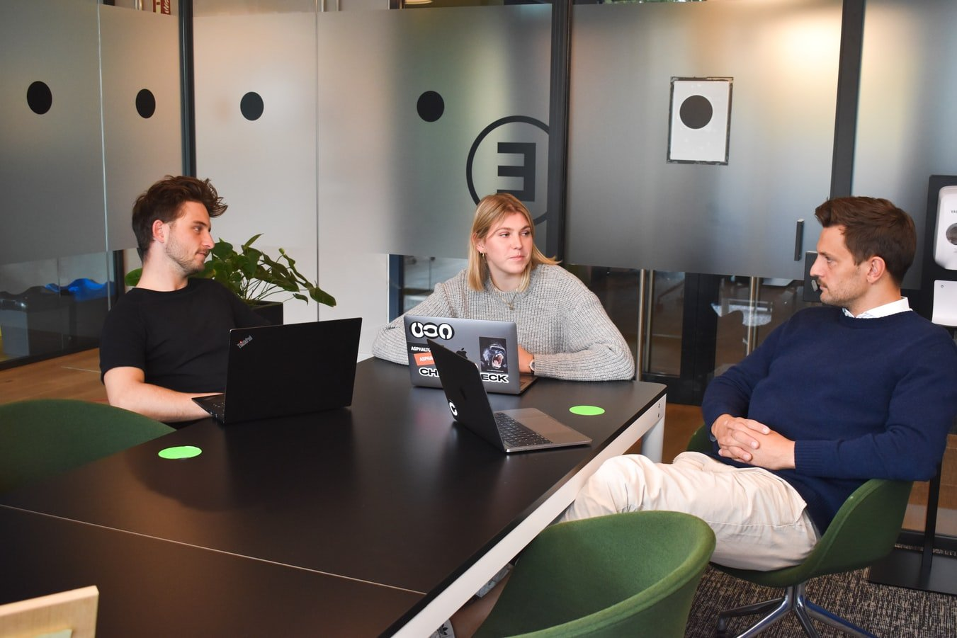 Three office workers in a meeting   Photo: Unsplash