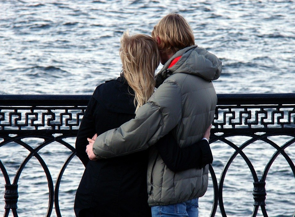 A couple hugging while looking at the sea. | Photo: Pixabay